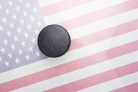 hockey games: vintage old hockey puck is on the ice with united states of america flag