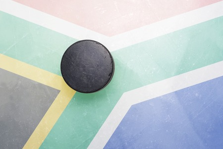 south africa flag: vintage old hockey puck is on the ice with south africa flag Stock Photo