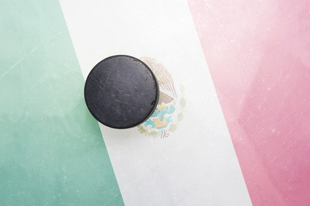 vintage old hockey puck is on the ice with mexico flag