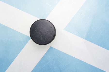 vintage old hockey puck is on the ice with scotland flag