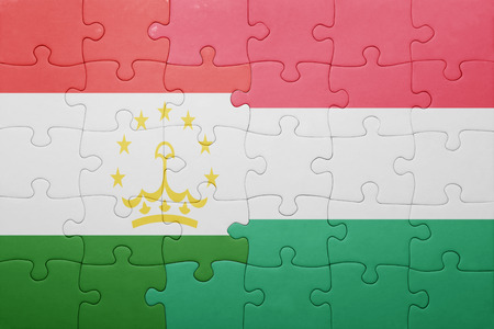 economy of tajikistan: puzzle with the national flag of tajikistan and hungary . concept Stock Photo