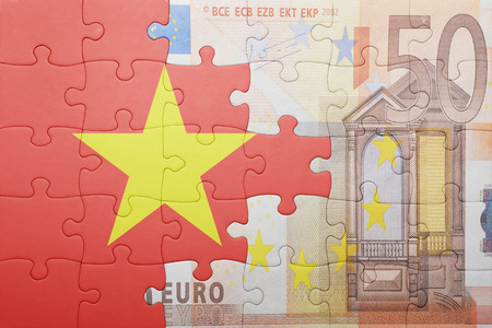 european integration: puzzle with the national flag of vietnam and euro banknote . concept Stock Photo