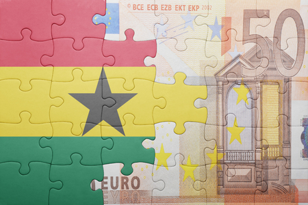 european integration: puzzle with the national flag of ghana and euro banknote . concept