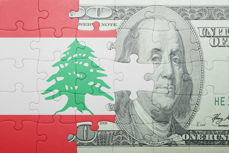 middle east crisis: puzzle with the national flag of lebanon and dollar banknote . concept