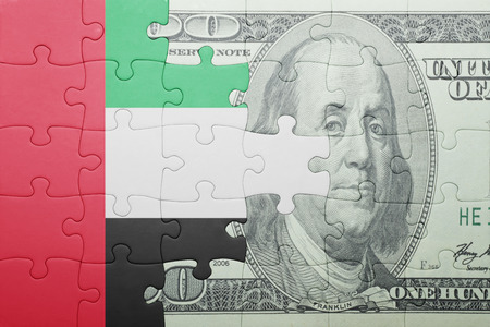 arabic currency: puzzle with the national flag of united arab emirates and dollar banknote . concept