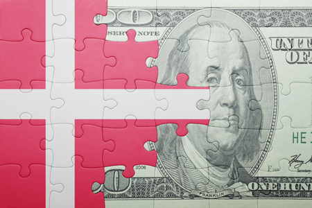 european integration: puzzle with the national flag of denmark and dollar banknote . concept