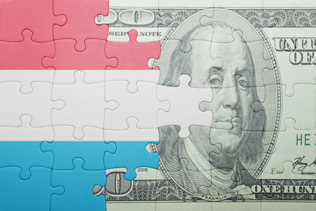 european integration: puzzle with the national flag of luxembourg and dollar banknote . concept