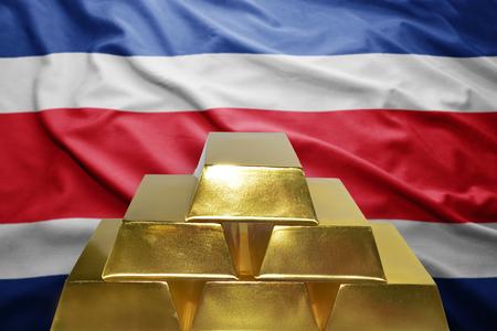 costa rica flag: shining golden bullions on the costa rica flag background