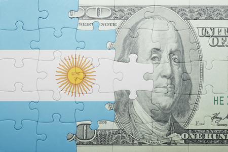bandera argentina: puzzle con la bandera nacional de Argentina y el billete de d�lar. concepto