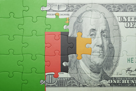 zambian: puzzle with the national flag of zambia and dollar banknote . concept