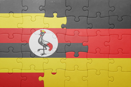 kampala: puzzle with the national flag of germany and uganda . concept