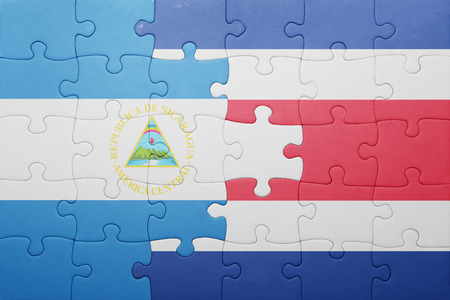 national flag: puzzle with the national flag of costa rica and nicaragua . concept
