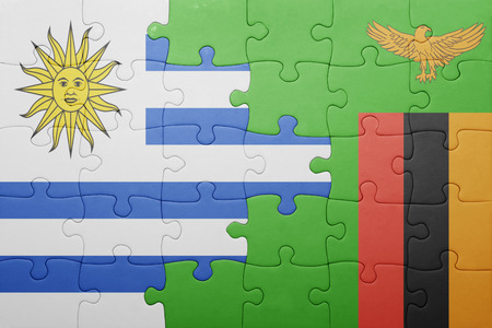 zambian flag: puzzle with the national flag of zambia and uruguay . concept Stock Photo