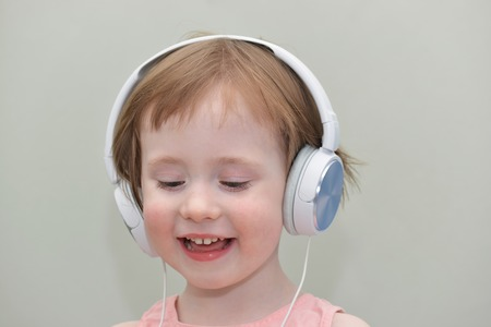 mugging: funny little girl with headphones on a gray background Stock Photo