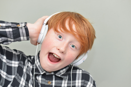 laughable: funny red haired boy with headphones on a gray background