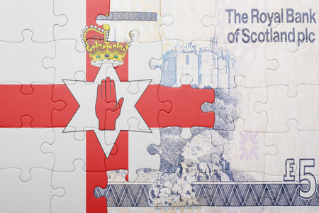 gb pound: puzzle with the national flag of northern ireland and scottish banknote . concept