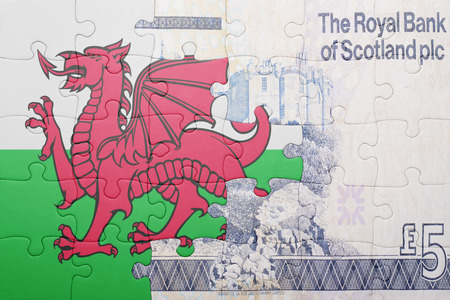 gb pound: puzzle with the national flag of wales and scottish banknote . concept