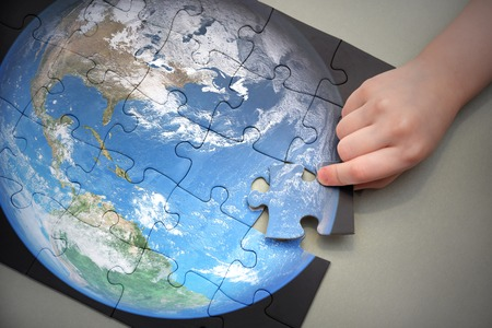 adds: Childs hand adds puzzle with planet earth. concept. elements of this image furnished by nasa Stock Photo