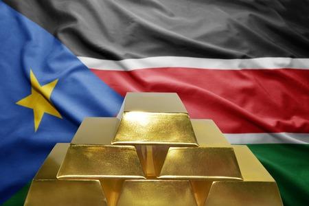 south sudan: shining golden bullions on the south sudan flag background