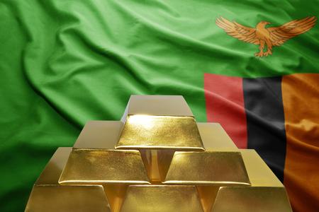 zambian flag: shining golden bullions on the zambian flag background