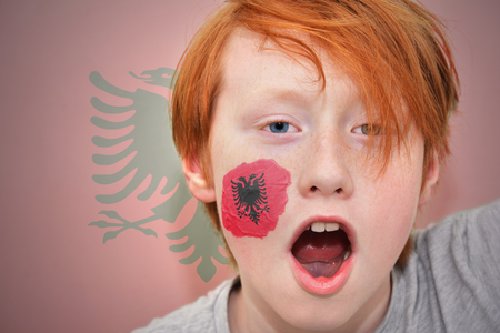 albanian: redhead fan boy with albanian flag painted on his face. on the albanian flag background
