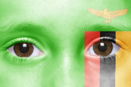zambian flag: humans face with zambian flag Stock Photo