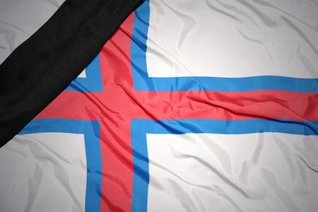 dole: waving national flag of faroe islands with black mourning ribbon
