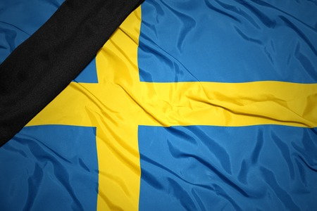 dole: waving national flag of sweden with black mourning ribbon Stock Photo