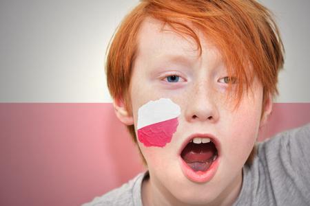 bandera de polonia: chico pelirrojo ventilador con bandera polaca pintada en la cara. en el fondo de la bandera polaca Foto de archivo