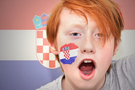 croatian: redhead fan boy with croatian flag painted on his face. on the croatian flag background Stock Photo