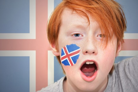 icelandic flag: redhead fan boy with icelandic flag painted on his face. on the icelandic  flag background