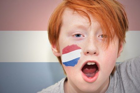 dutch: redhead fan boy with dutch flag painted on his face. on the  dutch flag background