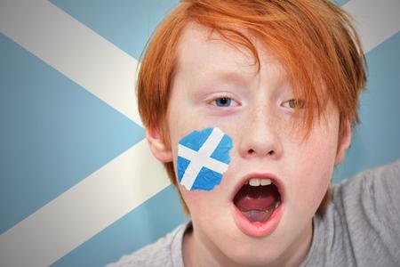 scottish flag: rossa ragazzo Fan con bandiera scozzese dipinta sul suo volto. sullo sfondo bandiera scozzese