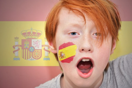 redhead fan boy with spanish flag painted on his face. on the spanish  flag background