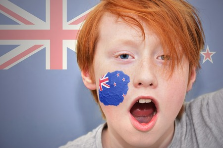 new zealand flag: redhead fan boy with new zealand flag painted on his face. on the new zealand flag background Stock Photo