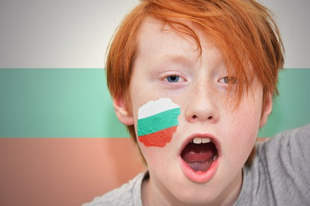 bulgarian: redhead fan boy with bulgarian flag painted on his face. on the bulgarian flag background Stock Photo