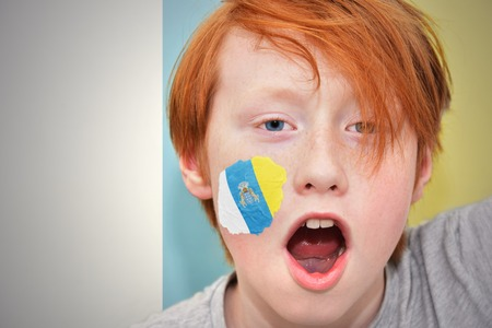 canarian: redhead fan boy with canarian flag painted on his face. on the canarian flag background Stock Photo