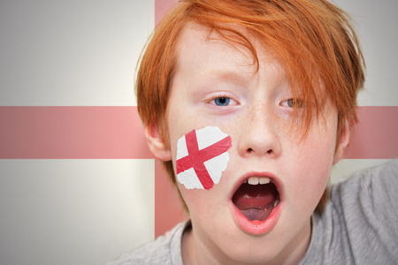 clash: redhead fan boy with english flag painted on his face. on the english flag background