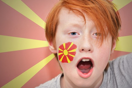 macedonian flag: redhead fan boy with macedonian flag painted on his face. on the macedonian flag background