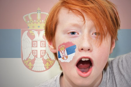 serbian: redhead fan boy with serbian flag painted on his face. on the serbian flag background