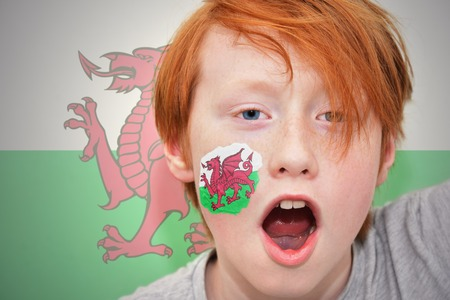 welsh flag: redhead fan boy with welsh flag painted on his face. on the  welsh flag background Archivio Fotografico