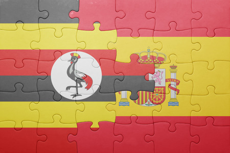 kampala: puzzle with the national flag of spain and uganda . concept
