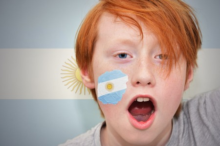 argentinean: redhead fan boy with argentinean flag painted on his face. on the  argentinean flag background