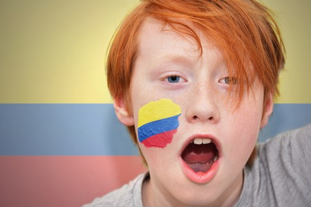colombian flag: redhead fan boy with colombian flag painted on his face. on the colombian  flag background Stock Photo