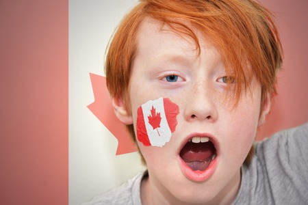 canadian football: redhead fan boy with canadian flag painted on his face. on the canadian  flag background