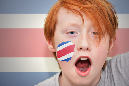 costa rican: redhead fan boy with costa rican flag painted on his face. on the  costa rican flag background