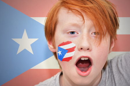 puerto rican flag: redhead fan boy with puerto rican flag painted on his face. on the  puerto rican flag background