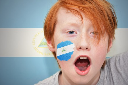 nicaraguan: redhead fan boy with nicaraguan flag painted on his face. on the nicaraguan  flag background