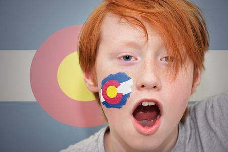 colorado state: redhead fan boy with colorado state flag painted on his face. on the colorado state flag background
