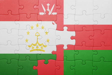 economy of tajikistan: puzzle with the national flag of tajikistan and oman . concept Stock Photo